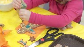 Stäng sig upp av ungen som dekorerar pepparkakakakorna lager videofilmer