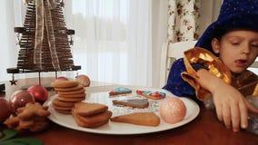 Stäng sig upp av ungen som dekorerar pepparkakakakorna, glad jul lager videofilmer