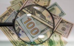 Stäng sig upp av USA sedlar, 100 oss zoomen för dollaranmärkningsinsidan av förstoringsglaset Royaltyfri Bild