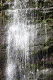 Stäng sig upp av vatten som applåderar ner en vattenfall Arkivfoto