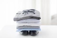 Stäng sig upp av vikta manliga skjortor och skor på tabellen Arkivfoto