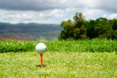 Stäng sig upp av vit golfboll på orange utslagsplats på grönt gräs med blå himmel och molnet och sikten av bergbakgrund i solig d Arkivfoton