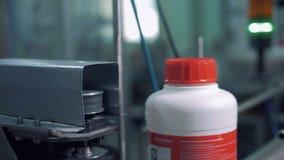 Stäng sig upp av vita plast- flaskor som fortskrider transportören stock video