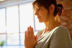 Stäng sig upp av yogikvinnan som mediterar på yogastudion royaltyfri bild