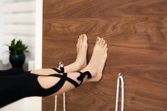 Stäng sig upp ben på väggen medan övande yoga för kvinnan på rep som sträcker i idrottshall Passform- och wellnesslivsstil royaltyfri foto