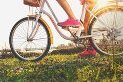 stäng sig upp benkvinna på cykeln med solnedgång Fotografering för Bildbyråer