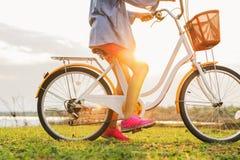 stäng sig upp benkvinna på cykeln med solnedgång Royaltyfria Foton