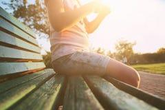 Stäng sig upp bild av barnsammanträde på bänk under solnedgång arkivfoto