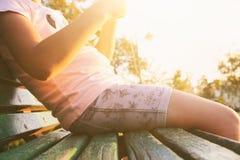 Stäng sig upp bild av barnsammanträde på bänk under solnedgång royaltyfri fotografi