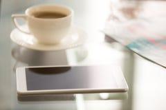Stäng sig upp bild av den moderiktiga smartphonen på det glass skrivbordet Arkivbilder