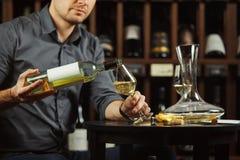 Stäng sig upp bild av hällande vitt vin för sommelieren från flaskan i exponeringsglas Royaltyfri Foto