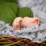 Stäng sig upp bild av nyfött behandla som ett barn fot på den stack plädet i en watt Royaltyfri Bild
