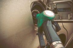 Stäng sig upp bilden av den moderna bilen som tankar på en bensinstation Tonad bild med Co Arkivbild