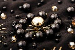 Stäng sig upp blomman av guld- och svarta pärlor på den svarta textilen Arkivfoton