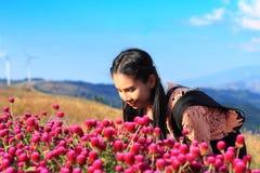 Stäng sig upp caucasian kvinna- och uttryckslycka, nätt flicka med rosa Gomphrenablommor royaltyfri fotografi