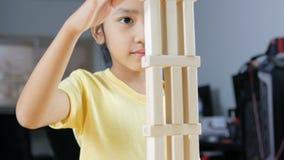 Stäng sig upp den asiatiska lilla flickan för skottet som spelar trätegelstenleksaken lager videofilmer