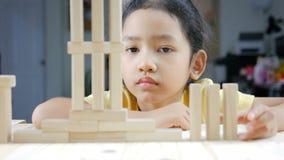 Stäng sig upp den asiatiska lilla flickan för skottet som spelar trätegelstenleksaken arkivfilmer