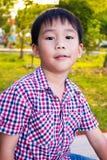 Stäng sig upp den asiatiska pojken som kopplar av i parkera för unge barn utomhus Fotografering för Bildbyråer