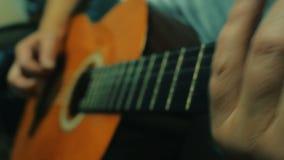 Stäng sig upp den bästa sikten som skjutas av mannen som spelar gitarren 4K stock video