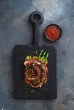 Stäng sig upp den bläckfisktentakelwithpotatoes och citronen på den svarta plattan Arkivfoton