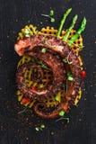 Stäng sig upp den bläckfisktentakelwithpotatoes och citronen på den svarta plattan Arkivfoto