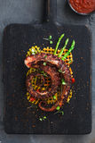 Stäng sig upp den bläckfisktentakelwithpotatoes och citronen på den svarta plattan Fotografering för Bildbyråer