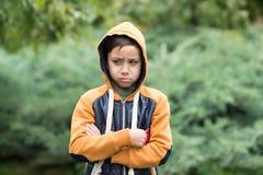 Stäng sig upp den emotionella ståenden av en skolpojke i ett gult omslag T royaltyfri fotografi