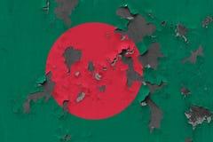 Stäng sig upp den grungy, skadade och red ut Bangladesh flaggan på väggen som skalar av målarfärg för att se inom yttersida royaltyfri foto