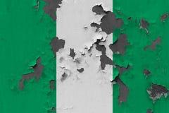 Stäng sig upp den grungy, skadade och red ut Nigeria flaggan på väggen som skalar av målarfärg för att se inom yttersida stock illustrationer