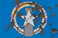 Stäng sig upp den grungy, skadade och red ut nordliga Mariana Islands flaggan på väggen som skalar av målarfärg för att se inom y stock illustrationer