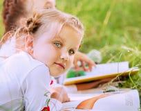 Stäng sig upp den gulliga lilla flickan för ståenden som läser en bok arkivfoton