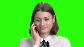 Stäng sig upp den härliga flickaståenden som flörtar på telefonen stock video