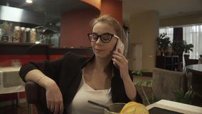 Stäng sig upp den härliga framsidakvinnan som talar vid smartphonen på inomhus bakgrund arkivfilmer