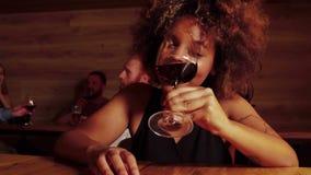 Stäng sig upp den härliga sexiga unga svarta kvinnan som dricker rött vin i stång Henne godlynt ` s och skratt lager videofilmer