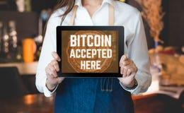 Stäng sig upp den hållande minnestavlan för kvinnabaristaen och visa accepterad bitcoin fotografering för bildbyråer
