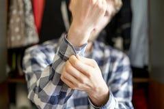 Stäng sig upp den hemmastadda pålagda tillfälliga skjortan för den unga mannen och att justera en knapp muffslutet upp f royaltyfri foto