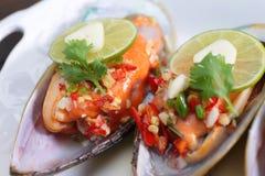 Stäng sig upp den kryddiga musslan med limefrukt och vitlök, selektiv fokus Royaltyfri Fotografi