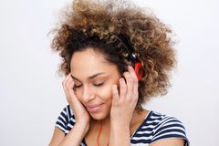 Stäng sig upp den lyckliga afrikansk amerikanflickan som lyssnar till musik med hörlurar arkivbild