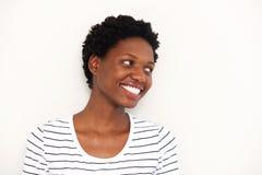 Stäng sig upp den lyckliga afrikanska kvinnan som bort ler och ser vid vit bakgrund Arkivbild