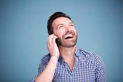 Stäng sig upp den lyckliga mannen som talar på mobiltelefonen och ser upp Arkivfoton