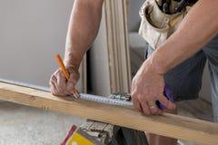 Stäng sig upp den manliga konstruktörsnickaren eller byggmästarehanddetaljen som arbetar och mäter trä i industriellt konstruktio royaltyfri fotografi