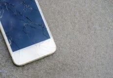 Stäng sig upp den moderna mobiltelefonen med den brutna skärmen på asfaltvägen Arkivbilder