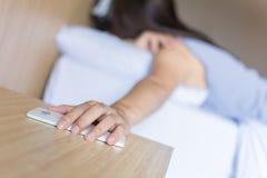 Stäng sig upp den rörande smartphonen för handen på trätabellen och kvinna på den selektiva fokusen för säng Arkivbild