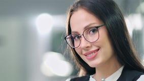 Stäng sig upp den stilfulla kvinnliga kontorsarbetaren för ståenden som sätter på exponeringsglas som tycker om och ler lager videofilmer