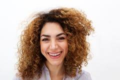 Stäng sig upp den unga kvinnan med lockigt hår som ler förödmjuka vit bakgrund royaltyfria bilder