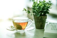 Stäng sig upp den varma koppen för svart te på trätabellen, i att bo ro Arkivfoto