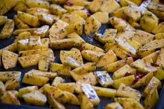 Stäng sig upp den varma kryddiga potatisen med örter på en bakplåt Royaltyfri Bild