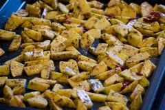 Stäng sig upp den varma kryddiga potatisen med örter på en bakplåt Fotografering för Bildbyråer