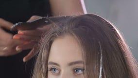Stäng sig upp den yrkesmässiga frisören, stylisten som färgar tonårigt flickahår lager videofilmer