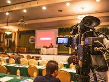 Stäng sig upp den yrkesmässiga videokameran i konferenskorridor eller seminarium royaltyfria bilder